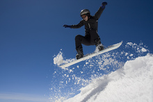Fototapeta - Snowboarder Jumping through Air